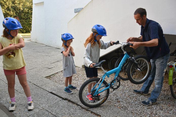 Bart aide ses enfants à sortir leurs vélos.