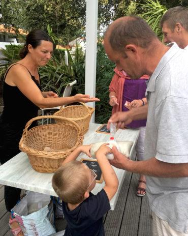 Une paludière est venu présenter ses produits aux vacanciers. Dominique et son fils achètent du sel avec Damien.